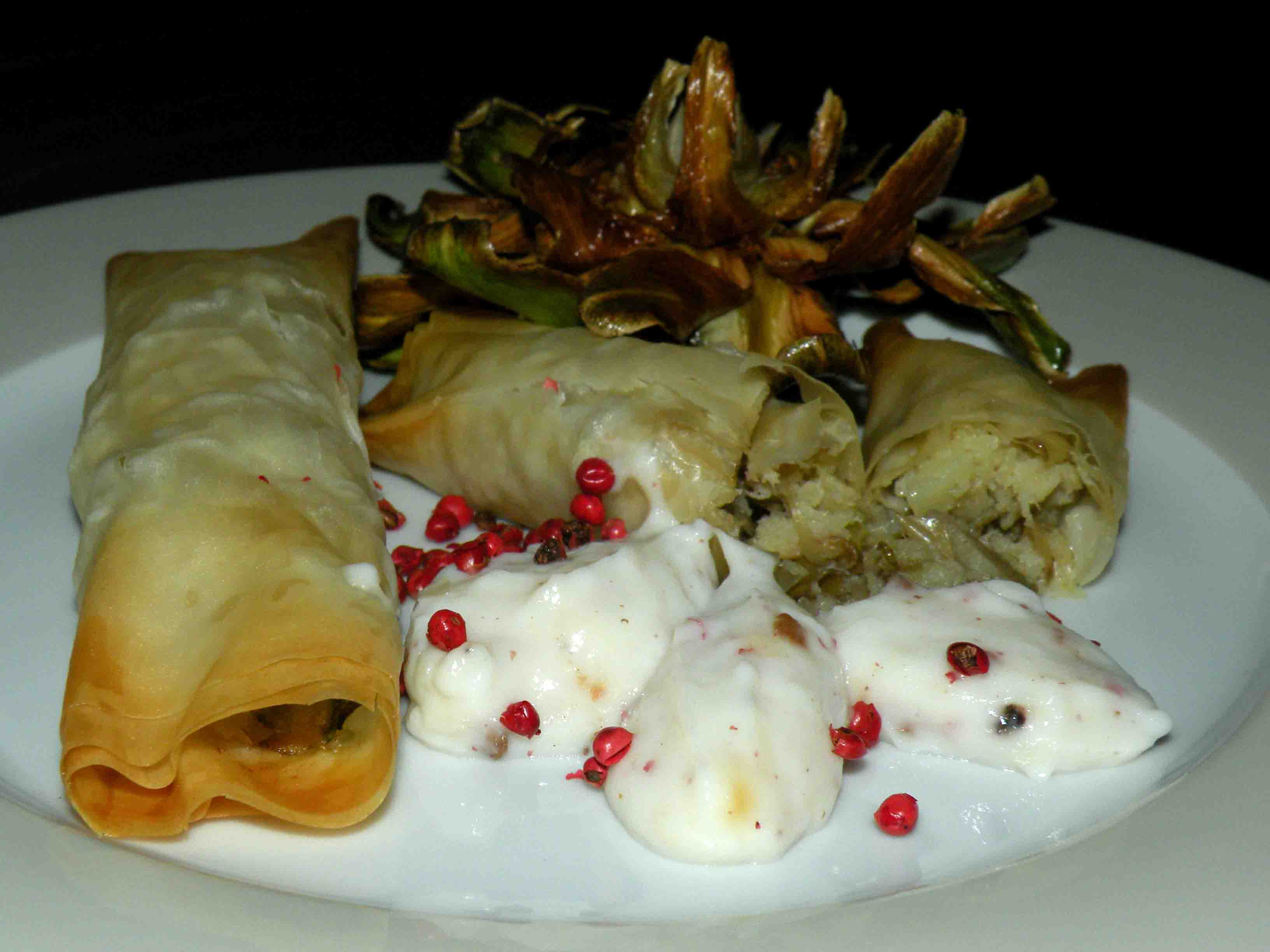 Rolls of phyllo dough filled with perch, artichokes and zucchini with pink pepper-cream